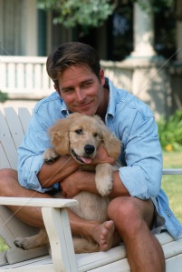 man-holding-a-puppy-outdoors-in-a-chair